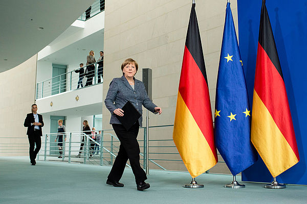 Angela Merkel with the flags of Germany and Europe